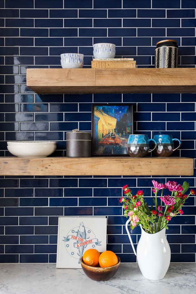 small kitchen design with blue subway tile backsplash and wood shelving