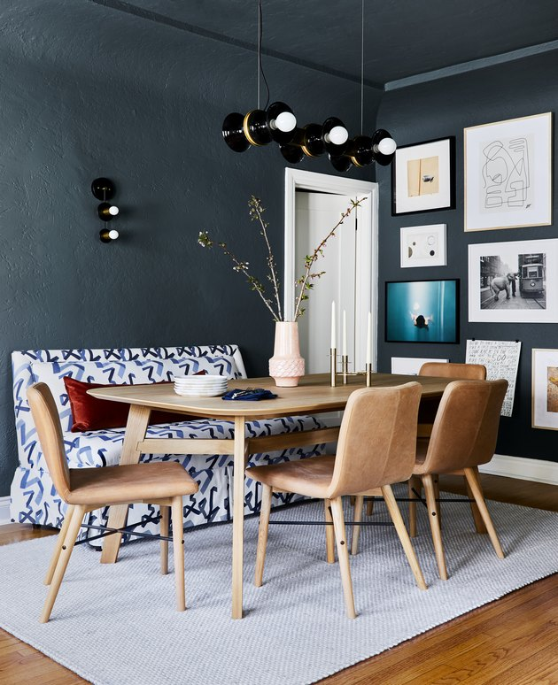 dining room lighting idea with chandelier above table and wall sconce on blue walls