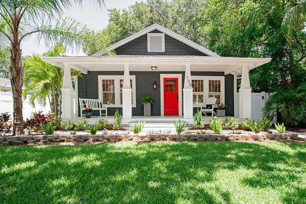 craftsman house with white eaves and a red door