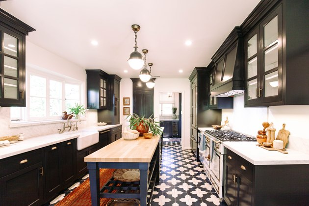 Kitchen with blue and white floor tile, dark blue cabinets, pendant lights and vintage stove