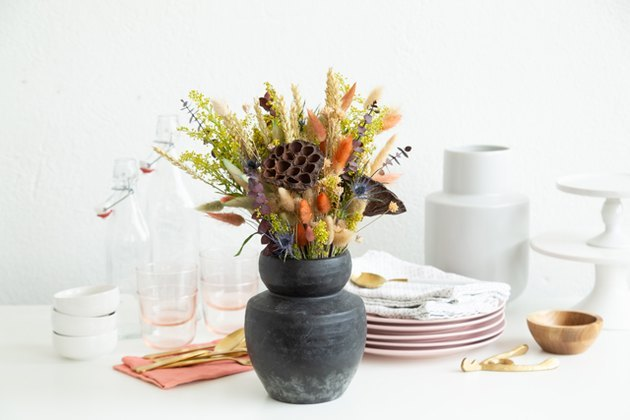 Dried floral arrangement with black clay vase on table with dishes.
