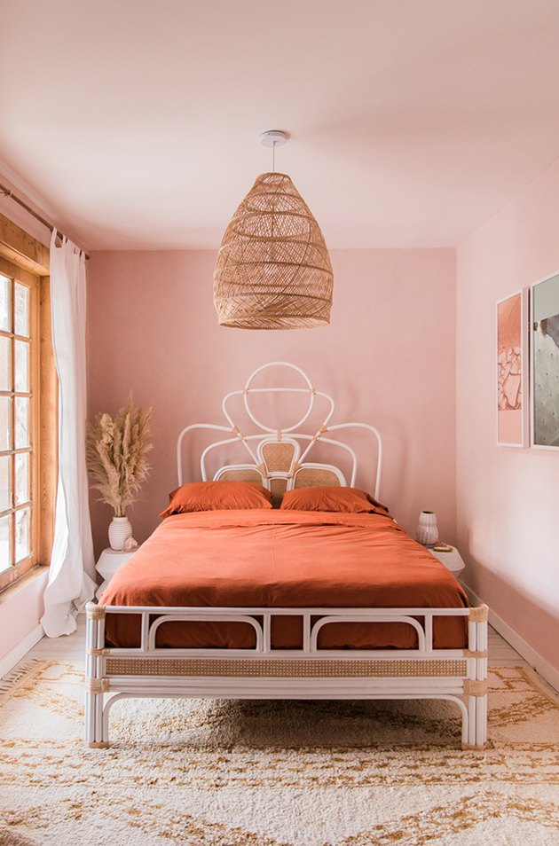 Sunset-hued pink bedroom with woven bohemian pendant and rattan bed frame