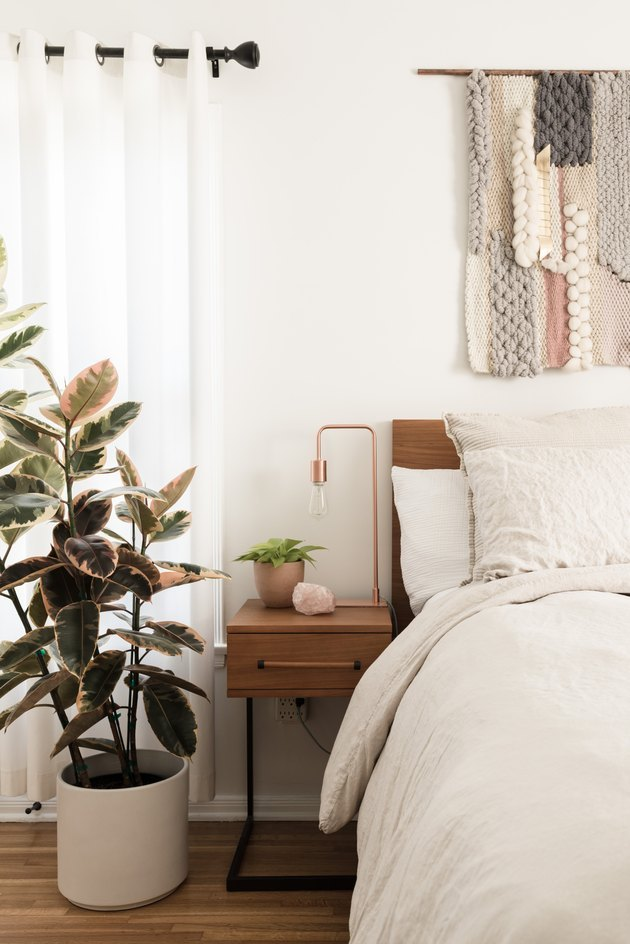 bedroom with plant and wall hanging
