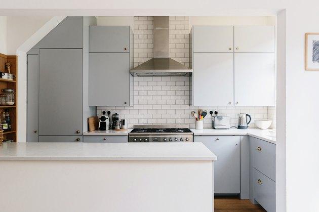 Subway tile backsplash in kitchen with light blue cabinets.