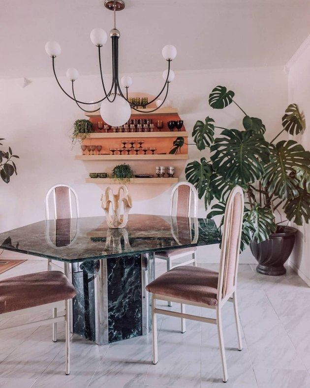 Dining room with sunset-inspired shelving accent and geometric marble dining table