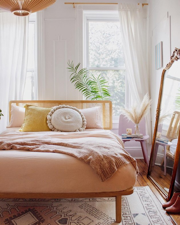 Sunset-inspired bedroom with drapery at windows and framed mirror leaning against the wall