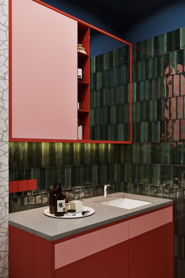 bathroom with red vanity cabinet and green textured tile walls