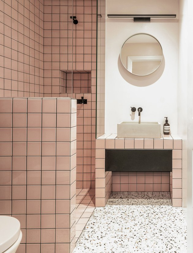 concrete trough bathroom sink in pink tiled bathroom with terrazzo flooring