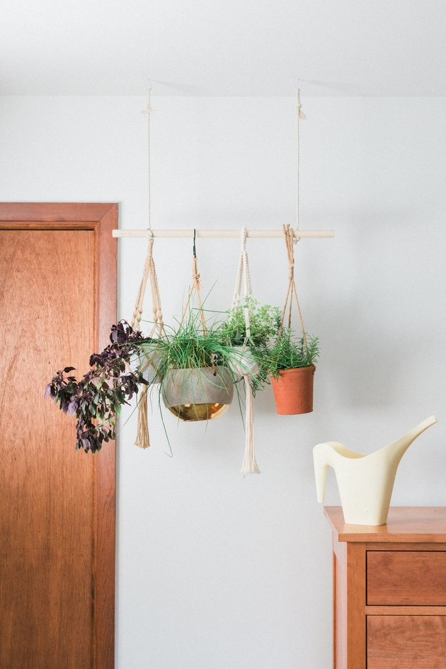 Slip the hanging potted herbs onto the dowel rod between the rope.