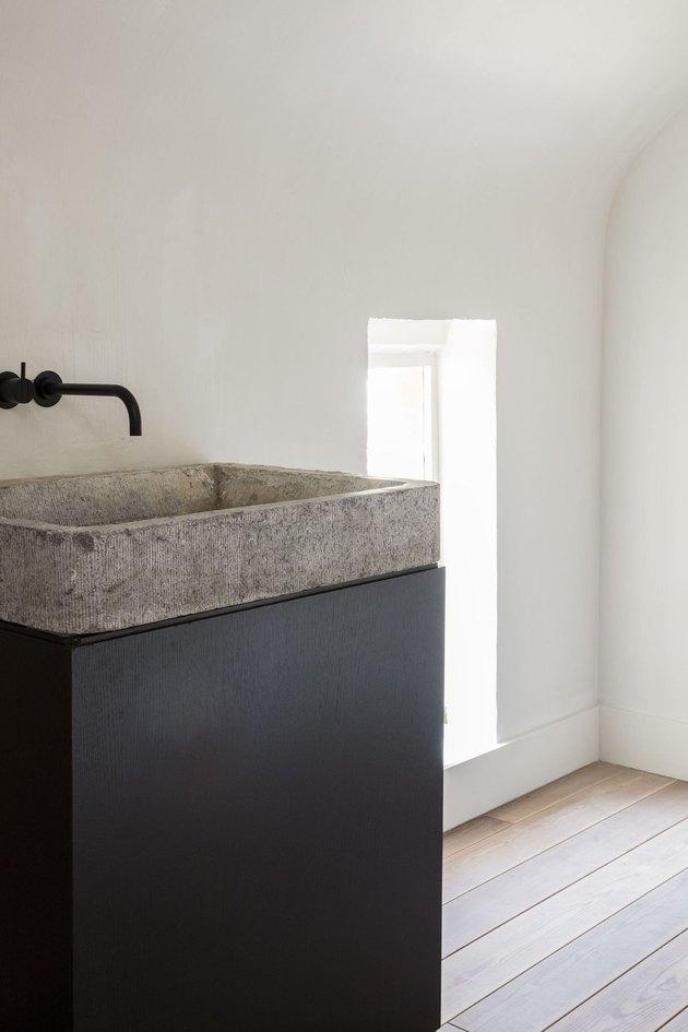 textured concrete bathroom sink on black pedestal