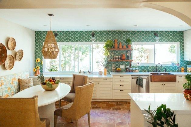 green tile backsplash with white cabinets and terra cotta kitchen flooring