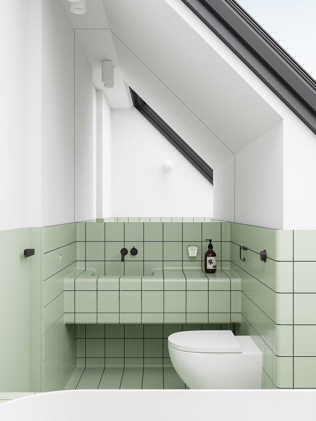 white bathroom with pistachio green tiles and tile countertop