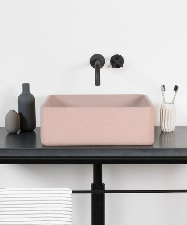 blush pink concrete bathroom sink with black fixtures