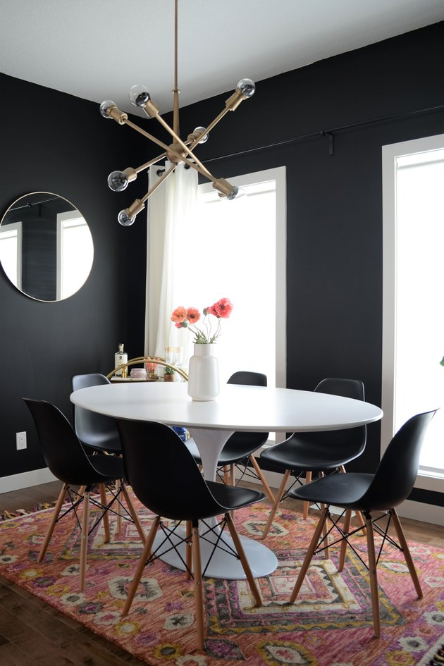 black dining room color idea with brass lighting and black chairs