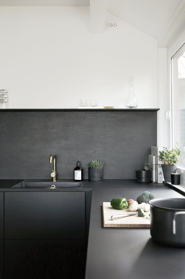black and white kitchen with black backsplash and sink