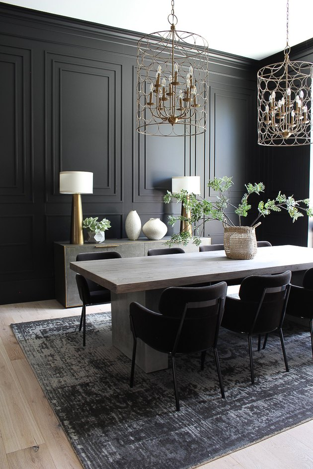 black dining room color idea with paneled walls and brass accents