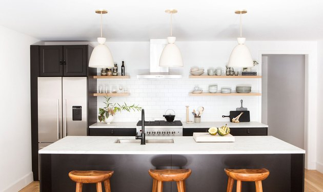 black and white kitchen with open shelving and white pendant lighting
