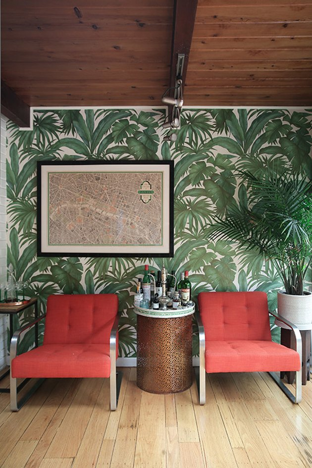 tropical wallpaper with red lounge chairs and wood beam ceiling