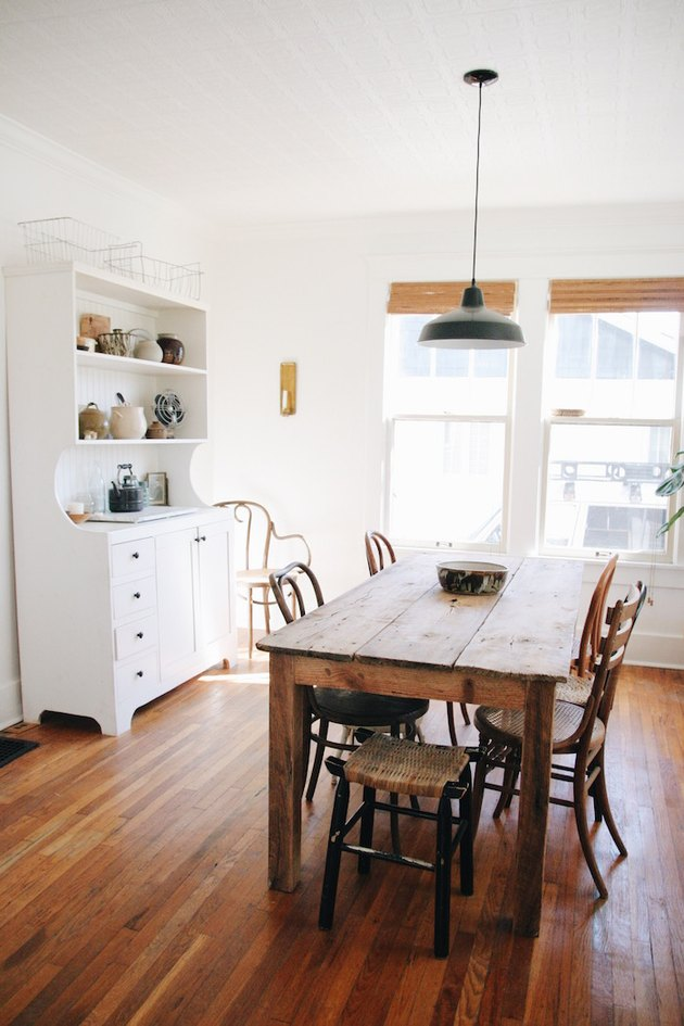 industrial dining room idea with white walls and wooden table