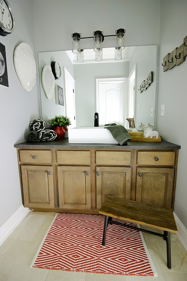 dark gray laminate bathroom countertop on rustic vanity cabinet in farmhouse bathroom