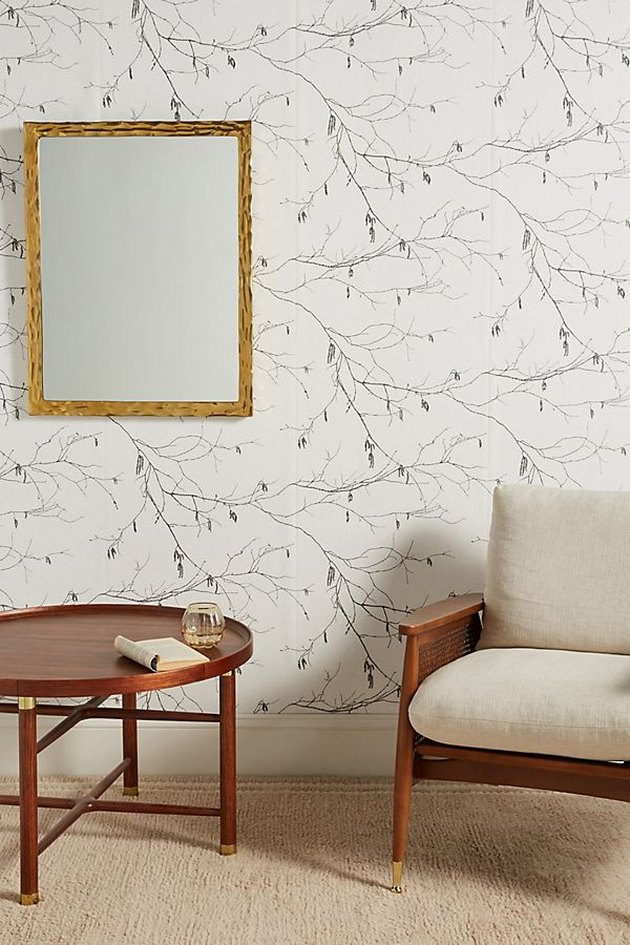 white wallpaper wall with table, mirror, and chair