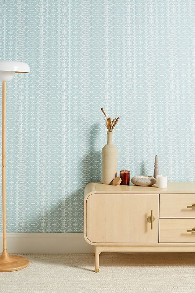 blue wallpaper wall with dresser and lamp