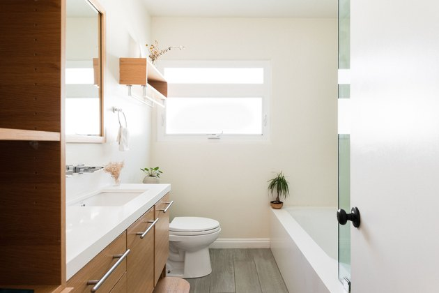 bathroom with wood vanity, wood flooring, white toilet, over-the-toilet wood shelf, bathtub with glass shower door, small plant on the ledge of the tub