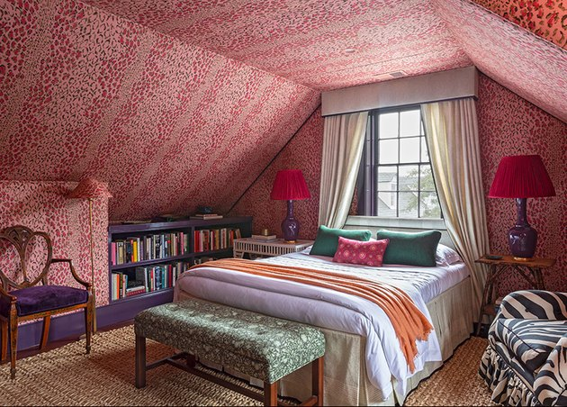 bold red and pink patterned bedroom with drapery over bed