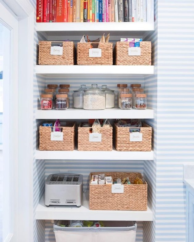 small pantry with woven storage bins and blue and white wallpaper