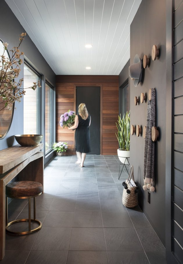 This hallway in New York brings dark and light together with wood paneling and a slate floor