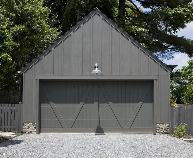 Detached Garage Ideas with stone and black wood detached garage with black dual garage doors.