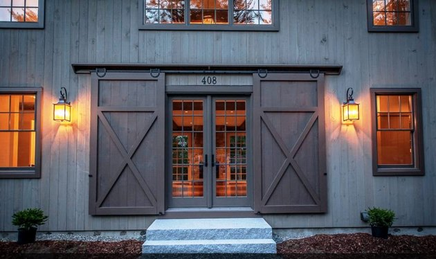 Dark wood Contemporary Barn Doors outside of modern barn house with french door entry.