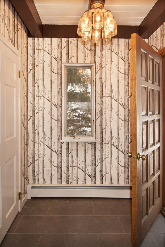 Hallway with pendant light and wallpaper with a trees design