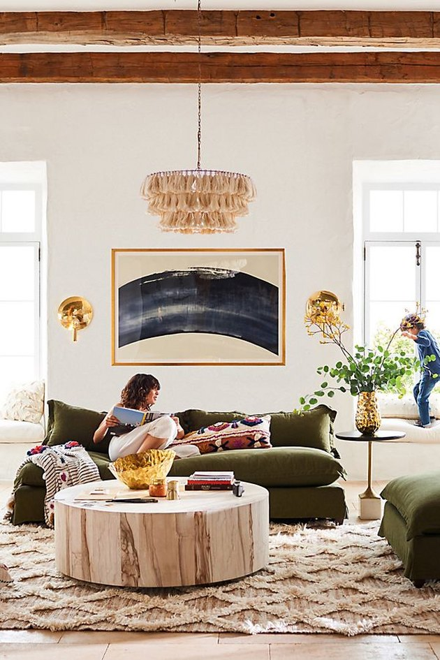 bohemian living room lighting idea with tasseled chandelier above green sofa