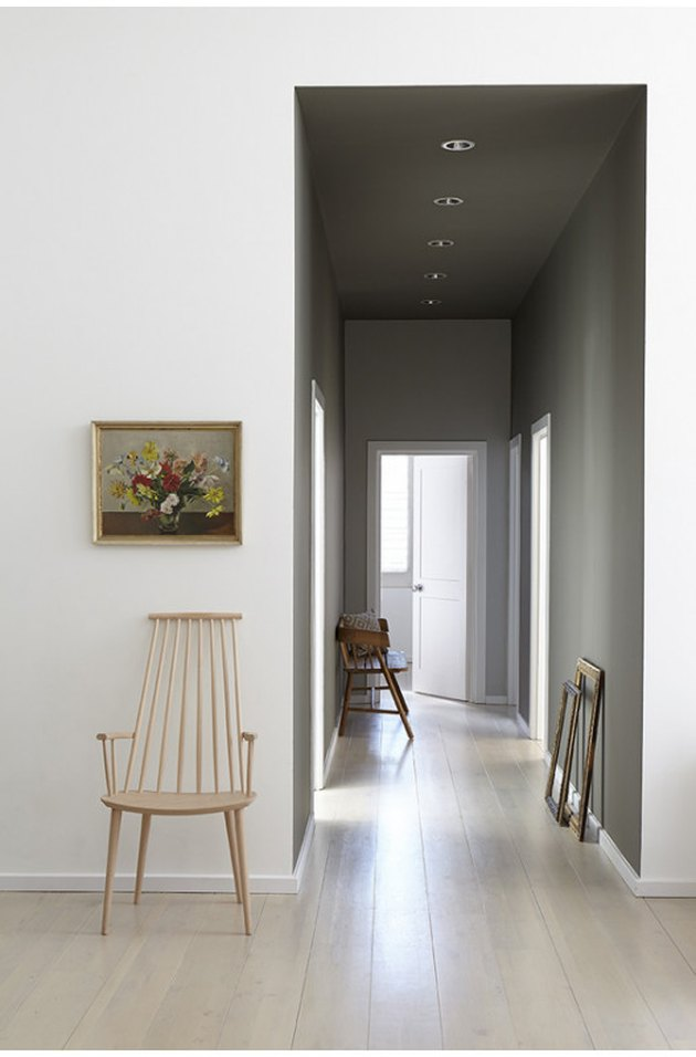 A hallway with subtle Scandinavian vibes, dark paint, and cool tones.
