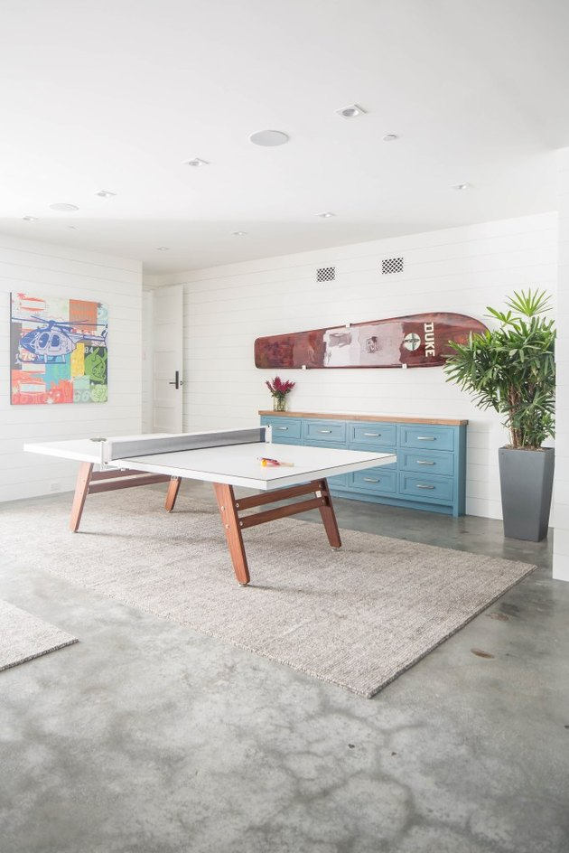 neutral garage game room ideas with table tennis and statement art