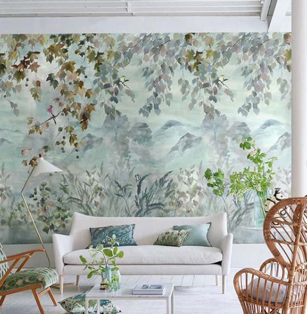 landscape mural living room wallpaper idea with white sofa and rattan chair