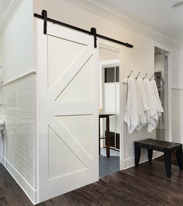 White Contemporary Barn Doors white subway tile, dark wood floors, black wood bench, white towels in hooks.