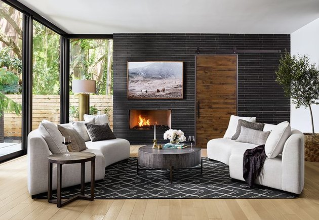 Contemporary Barn Doors in room with Black brick wall with fireplace, rustic wood barn door, matching curved beige couches, black area rug, light wood floors.