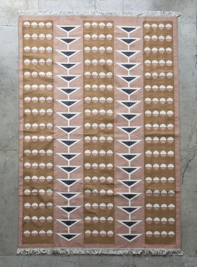 Beige and blush area rug with black accents and geometric striped design