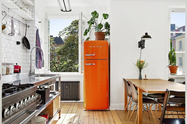 fresh and airy kitchen color idea with bright orange fridge