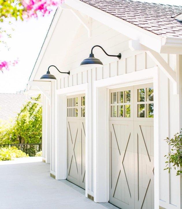 Cream barn garage doors with white exterior and black barn lights