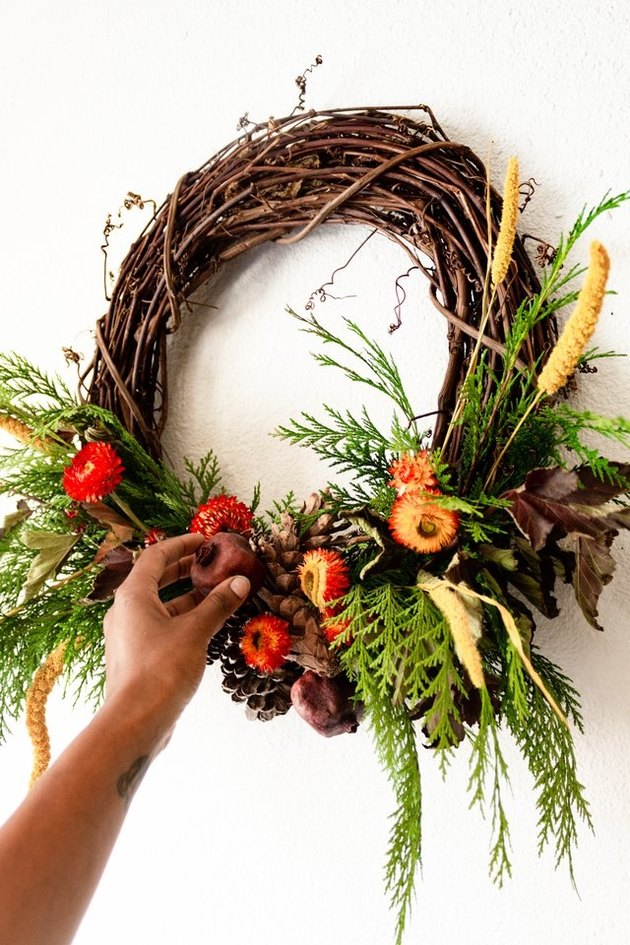 autumnal wreath with greenery, flowers, and pinecones