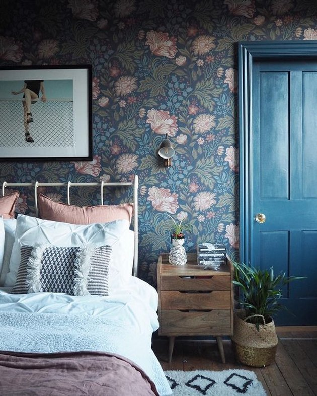 country bedroom idea with blue door and floral wallpaper