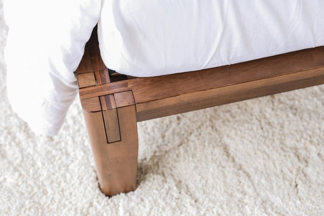 close up of bed frame with white sheet