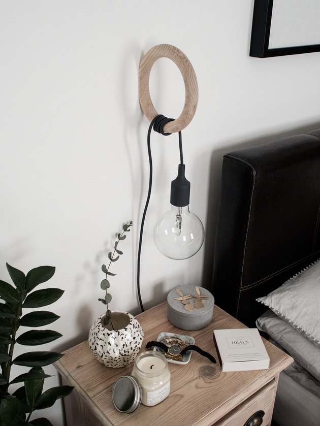 bedroom lighting idea with pendant wrapped around a wall hook at bedside