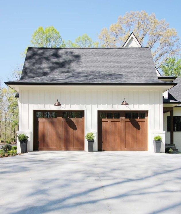 Wood barn garage doors with white farmhouse exterior