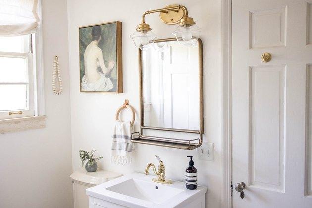 Brass vanity light fixture in bathroom