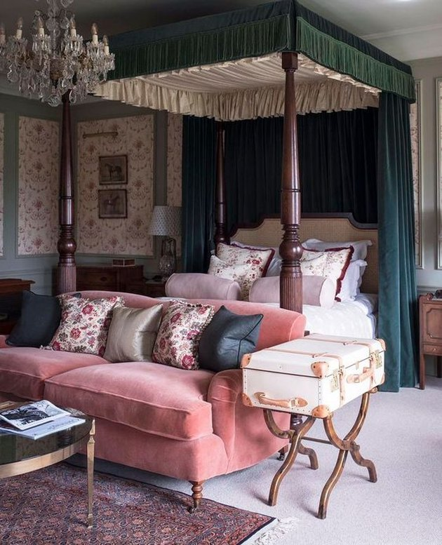 country bedroom idea with four poster bed with velvet curtains and velvet sofa