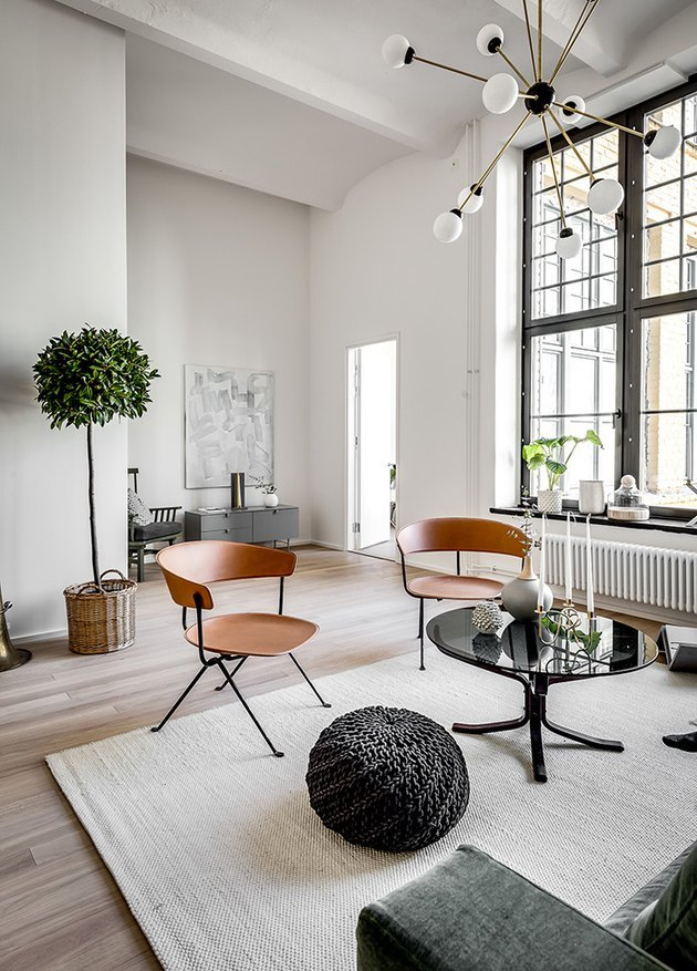 living room space with wood chairs, white walls, and sputnik lamp